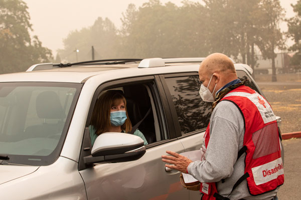 American Red Cross volunteer John Bergendahl speaks with Amanda Meyer as she arrives looking for a friend she hasn't heard since fleeing the wildfires in Oregon. The Jackson County Expo and Fairgrounds site is a Red Cross shelter in Central Point, OR.