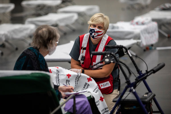 Emily Girard of the American Red Cross speaks with Sue Barnes at an American Red Cross shelter in Portland, OR on Monday, September 14, 2020 after evacuating because of wildfires burning throughout the region.