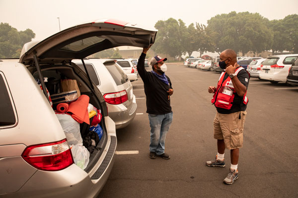 Eric Carmichael of the American Red Cross speaks with Jairo Gomez outside a shelter for people fleeing the wildfires in Oregon, at the Jackson County Expo and Fairgrounds in Central Point, OR on Sunday, September 13, 2020. Jairo, his wife and their three children fled the fires and got out just in time. Their home in Phoenix, Oregon was completed destroyed by the fires, the only possessions they have left are in the back of the car.
