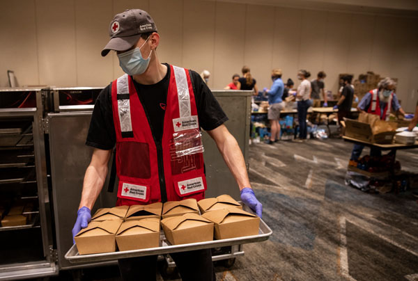 American Red Cross volunteer Kalen Pippins, helps to get meals ready to deliver to evacuees from the Oregon wildfires who are staying in hotel shelters in Eugene, OR