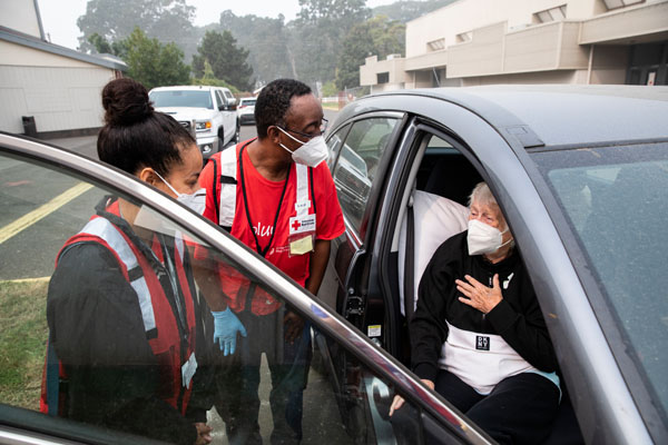 Leslie Sierra and Michael Watkins of the American Red Cross say goodbye to Juanita Ann Hamann on Sept. 15, 2020 as she leaves this Red Cross shelter. Juanita is moving to a hotel shelter also run by the Red Cross, in Salem, OR. Photo by Scott Dalton/American Red Cross.